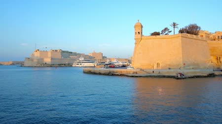 lápide : Explore fortified cities of Valletta Grand Harbour during the yacht trip - the huge rampart of Senglea with Guard Tower on the edge and Fort Saint Angelo of Birgu on the background, Malta.