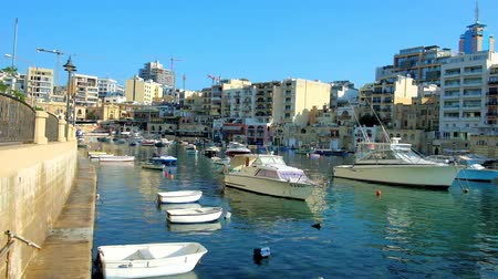 мальтийский : ST JULIANS, MALTA - JUNE 20, 2018: Enjoy the walk around Spinola Bay harbour with numerous fishing boats, white dinghies and traditional Maltese luzzu vessels, on June 20 in St Julians.