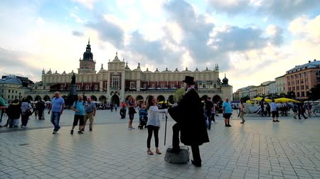 ator : KRAKOW, POLAND - JUNE 12, 2018:  Enjoy performance of mime artist in black vintage coat and cylinder hat in Main Market Square with Cloth Hall on the background, on June 12 in Krakow.