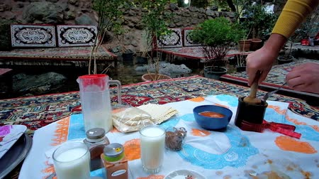 yoghurt : TEHRAN, IRAN - OCTOBER 25, 2017: Tasty abgusht (lamb soup-stew with chickpeas and vegetables) in stone pot (dizi) with flatbread in outdoor cafe of Darband, on October 25 in Tehran Stock Footage