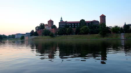 wawel : The rippled surface of Vistula river reflects the twilight sky and the medieval Wawel Castle, hidden behind the lush greenery of garden, Krakow, Poland. Stock Footage