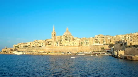 torre sineira : The medieval native limestone Valletta walls, edifices, St Pauls Anglican Pro-Cathedral and Carmelite Church, lighted with sun rays, become shiny golden, Malta.