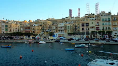 arquipélago : SENGLEA, MALTA - JUNE 18, 2018: The pleasant trip around medieval cities of Valletta Grand Harbour, numerous fishing boats and luzzu are moored at the shore of L-Isla, on June 18 in Senglea.
