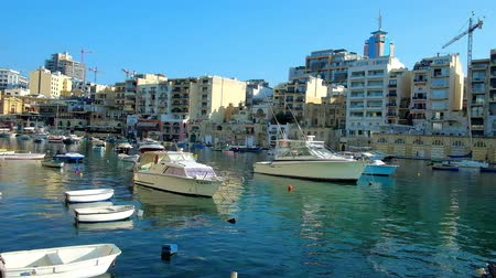 veleiro : ST JULIANS, MALTA - JUNE 20, 2018: Spinola Bay harbor with many small fishing boats and modern residential quarters on the background, on June 20 in St Julians.