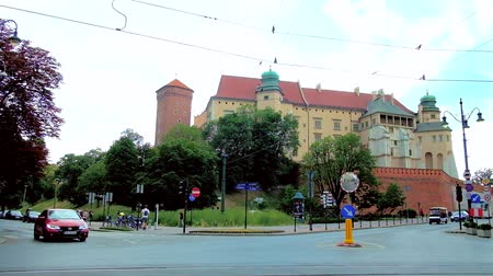 wawel : KRAKOW, POLAND - JUNE 21, 2018: The medieval huge Wawel Citadel surrounded by busy roads with fast traffic, the vintage blue tram turns to Stradomska street in front of Castle, on June 21 in Krakow.