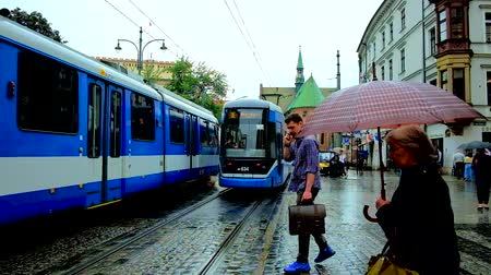 kamienice : KRAKOW, POLAND - JUNE 13, 2018: The modern blue tram in All Saints Square with a view on Church of St. Francis of Assisi on cold rainy weather, on June 13 in Krakow.