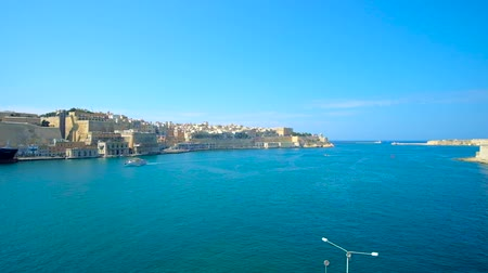 lom : Azure waters of Valletta Grand Harbour with medieval city architecture and the boats at its shore, Malta.