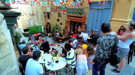 архипелаг : VALLETTA, MALTA - JUNE 19, 2018: The busy outdoor cafe during the games of FIFA World Cup Russia, the fans watch TV and enjoy their time spending with drinks and snacks, on June 19 in Valletta.