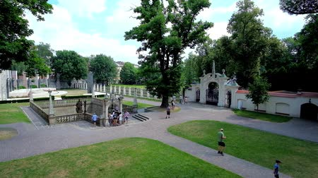 piskopos : KRAKOW, POLAND - JUNE 21, 2018: Garden of St Stanislaus Church at Skalka with Well-fountain of St Stanislaus and the sculptural group of Altar of Three Millennia on background, on June 21 in Krakow Stok Video