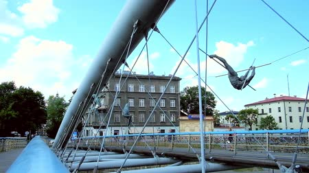 kazimierz : KRAKOW, POLAND - JUNE 21, 2018: Details of metal construction of modern Father Bernatek bridge across the Vistula river, decorated with acrobatic gravity-defying sculptures, on June 21 in Krakow.