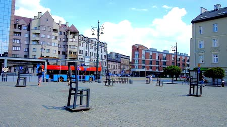cars traffic : KRAKOW, POLAND - JUNE 21, 2018: Walk along the Empty Chairs memorial of Jewish victims of World War 2, located in Ghetto Heroes Square, on June 21 in Krakow.