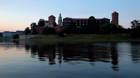 wawel : Romantic evening walk along the riverside park in Krakow with a view on Wawel Castle and its clear reflection in waters of Vistula, Poland.