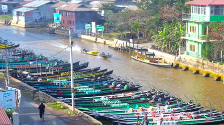 mianmar : NYAUNGSHWE, MYANMAR - FEBRUARY 19, 2018: The moored boats on canal of Inle Lake, stretching along the tourist village, on February 19 in Nyaungshwe. Stock Footage
