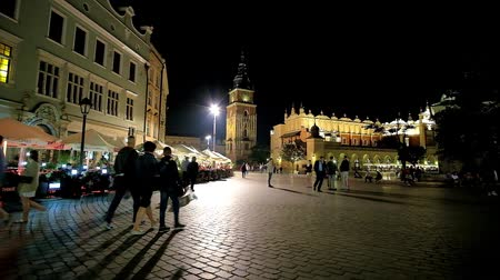 sukiennice : KRAKOW, POLAND - JUNE 12, 2018: The summer evening is perfect time to walk in Main Market Square with a view on Town Hall Tower, Cloth Hall and popular outdoor cafes, on June 12 in Krakow.