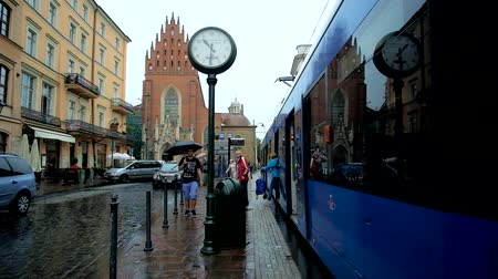 kamienice : KRAKOW, POLAND - JUNE 13, 2018: The tram station with vintage clock and Holy Trinity Basilica on background, All Saints Square, on June 13 in Krakow.