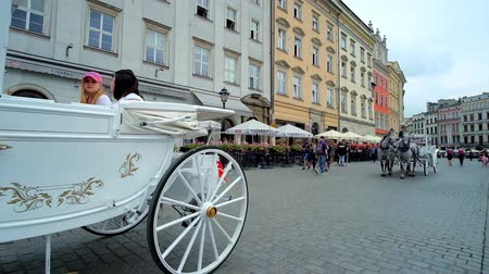 sukiennice : KRAKOW, POLAND - JUNE 13, 2018: The riding horse-drawn carriages attract the tourists to take a tour along the city center, starting from Main Market Square, on June 13 in Krakow