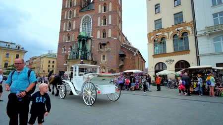 sukiennice : KRAKOW, POLAND - JUNE 13, 2018: The horse-drawn carriages ride along the crowded Plac Mariacki square with a view on St Marys Basilica and old townhouses around it, on June 13 in Krakow Stock Footage