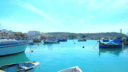 мальтийский : MARSAXLOKK, MALTA - JUNE 18, 2018: The morning Marsaxlokk Bay harbour is full of moored fishing boats and traditional Maltezze luzzu boats, on June 18 in Marsaxlokk.