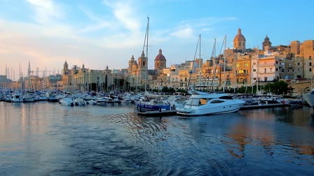tersane : BIRGU, MALTA - JUNE 18, 2018: The shipyards with moored yachts in Vittoriosa marina with a view on medieval Birgu with churches and mansions, lighted with sunset rays, on June 18 in Birgu.