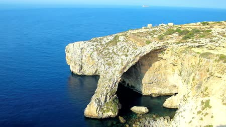 maltština : Visit Blue Grotto and enjoy idyllic nature and stunning landscapes of local rocky cliffs, surrounded by bright blue waters of Mediterranean sea, Malta.