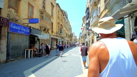 мальтийский : VALLETTA, MALTA - JUNE 19, 2018: The busy Merchants street is popular for the tourist souvenir stores, family shops, cafes and traditional workshops of local silversmiths, on June 19 in Valletta. Стоковые видеозаписи