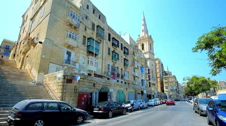 torre sineira : VALLETTA, MALTA - JUNE 19, 2018: The traffic along Marsamxett street with a view on historic housing and bell tower of St Paul Anglican Pro-Cathedral, on June 19 in Valletta