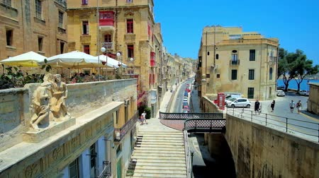 rampart : VALLETTA, MALTA - JUNE 19, 2018: Architecture of Liesse street with small pedestrian bridge of historic Victoria Gate, sculpture decoration of old edifice and outdoor cafes, on June 19 in Valletta Stock Footage