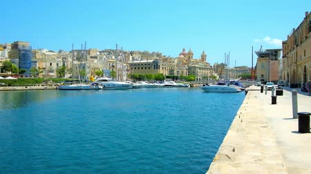 estaleiro : The joyful daily walk along the stone seaside promenade of medieval fortified city of Senglea (L-Isla) with a view on yachts in Vittoriosa marina and medieval edifices of Birgu, Malta. Stock Footage