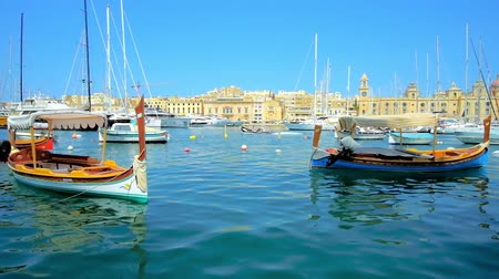 lápide : SENGLEA, MALTA - JUNE 19, 2018: The scenic wooden luzzu boats are traditional Maltese vessels, its easy to find them, walking along Senglea seaside promenade, on June 19 in Senglea.