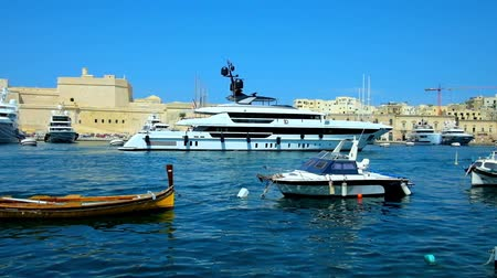 lápide : SENGLEA, MALTA - JUNE 19, 2018: The luxury modern yacht is parking at the walls of Fort St Angelo of medieval city of Birgu, surrounded by waters of Valletta Grand Harbour, on June 19 in Senglea.