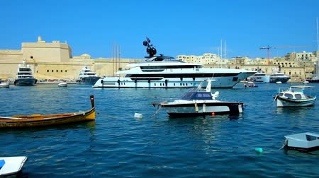 tersane : SENGLEA, MALTA - JUNE 19, 2018: Walk the seaside promenade with a view on Vittoriosa marina with splendid yachts, small boats and traditional luzzu vessels, on June 19 in Senglea.