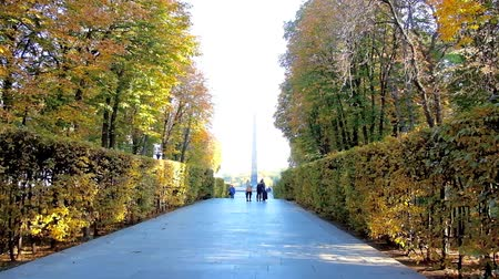 obelisco : KIEV, UKRAINE - OCTOBER 19, 2018: The alley in autumn Park of Eternal Glory leads to the Tomb of Unknown Soldier with tall stone Obelisk and Eternal Flame, on October 19 in Kiev.