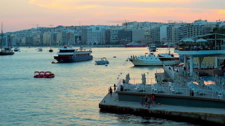 arquipélago : SLIEMA, MALTA - JUNE 19, 2018: Watch the sunset over the harbor, surrounded by modern residential and tourist neighborhoods, the ships and yachts are bobbing on the purple waters, on June 19 in Sliema