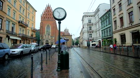 kamienice : KRAKOW, POLAND - JUNE 13, 2018: The retro tram station in All Saints Square is equipped with vintage clock for passengers, waiting their tram, on June 13 in Krakow.