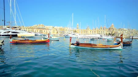 tersane : SENGLEA, MALTA - JUNE 19, 2018: Scenic luzzu boats, rocking on the gentle waves in Vittoriosa marina with a view on medieval Birgu and its shipyards with yachts on background, on June 19 in Senglea.