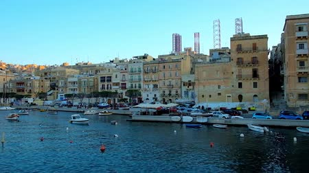 takımadalar : SENGLEA, MALTA - JUNE 18, 2018: The yacht trip along the coast of L-Isla with historic edifices, cozy cafes, luxury restaurants and numerous small boats, moored at the shore, on June 18 in Senglea. Stok Video