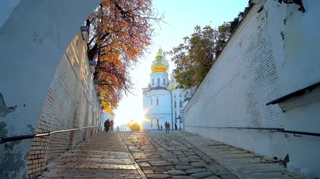 アセント : KIEV, UKRAINE - OCTOBER 19, 2018: The monks of Kiev Pechersk Lavra monastery go to Dormition Cathedral with a view on setting sun and bright autumn trees, on October 19 in Kiev.