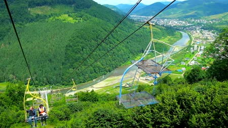 chairlift : MIZHHIRIA, UKRAINE - JULY 1, 2018: The chairlift on Makovytsia Mountain opens the great view on its gree slope and valley with running Rika River and Mizhhiria settlement, on July 1 in Mizhhiria.