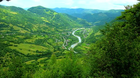 wood glade : The picturesque mountain landscape of Mizhhiria region from the top of Makovytsia mountain, the winding Rika river runs along the green valley, surrounded by villages and farms, Zakarpattya, Ukraine. Stock Footage