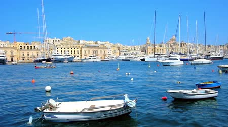lâmina : SENGLEA, MALTA - JUNE 19, 2018: Small boats and luxury yachts in Vittoriosa marina with a view on Birgu on background, on June 19 in Senglea.