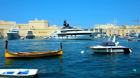 tersane : SENGLEA, MALTA - JUNE 19, 2018: The luxury yachts floats to its parking place in Vittoriosa Marina from Valletta Grand Harbour, on June 19 in Senglea. Stok Video