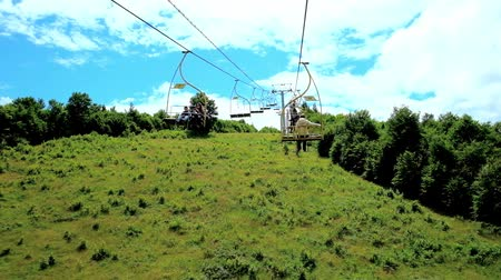 chairlift : MIZHHIRIA, UKRAINE - JULY 1, 2018: The slope of Makovytsia Mountain is covered with lush forest, tourists enjoy the views from the chairlift, stretching to the mountain peak, on July 1 in Mizhhiria.