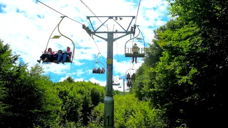 chairlift : MIZHHIRIA, UKRAINE - JULY 1, 2018: The ski lift chairs ride along the lush greenery of mountain forest, that covers the slopes of Makovytsia Mount, on July 1 in Mizhhiria.