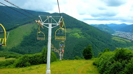 karpaty : MIZHHIRIA, UKRAINE - JULY 1, 2018: The ski lift of Makovytsia Mountain rides to the lower terminal along the scenic green slope, covered with forest, on July 1 in Mizhhiria. Dostupné videozáznamy