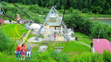 chairlift : MIZHHIRIA, UKRAINE - JULY 1, 2018: The view on lower terminal of the ski lift of Makovytsia Mountain, surrounded by lush greenery, on July 1 in Mizhhiria. Stock Footage