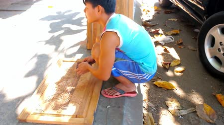 kínai negyed : YANGON, MYANMAR - FEBRUARY 17, 2018: The young carpenter works in Chinatown street, he finishes the carved door of cabinet, on February 17 in Yangon