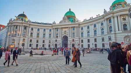 michael : VIENNA, AUSTRIA - FEBRUARY 17, 2019: The crowd of tourists in St Michael Square (Michaelerplatz) with a view on the St Michaels Wing of Baroque style Hofburg Palace, on February 17 in Vienna Stock Footage