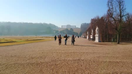 schonbrunn : VIENNA, AUSTRIA - FEBRUARY 19, 2019: Alley of Schonbrunn ornamental garden (Schlosspark) with line of antique style statues, flower beds and Gloriette on the hilltop, on February 19 in Vienna.
