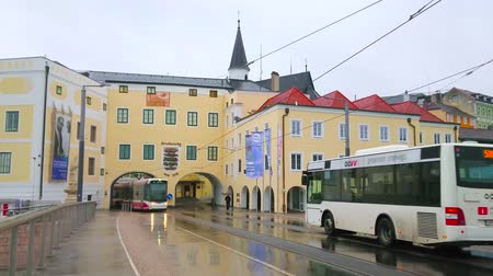 manor : GMUNDEN, AUSTRIA - FEBRUARY 22, 2019: The modern tram drives on the Traun bridge (Traunbrucke) through the small arch in K-Hof (Kammerhofmuseen) historic edifice, on February 22 in Gmunden.