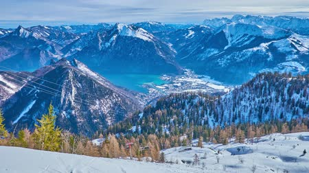 vacations cones : The peak of Feuerkogel mount overlooks the snowbound cones of Alp Dachstein massif, slopes with ski pistes and the Traunsee lake in valley, Ebensee, Salzkammergut, Austria.